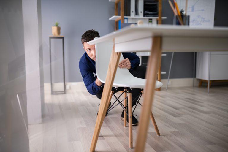 Afraid Businessman Peeking Behind Chair